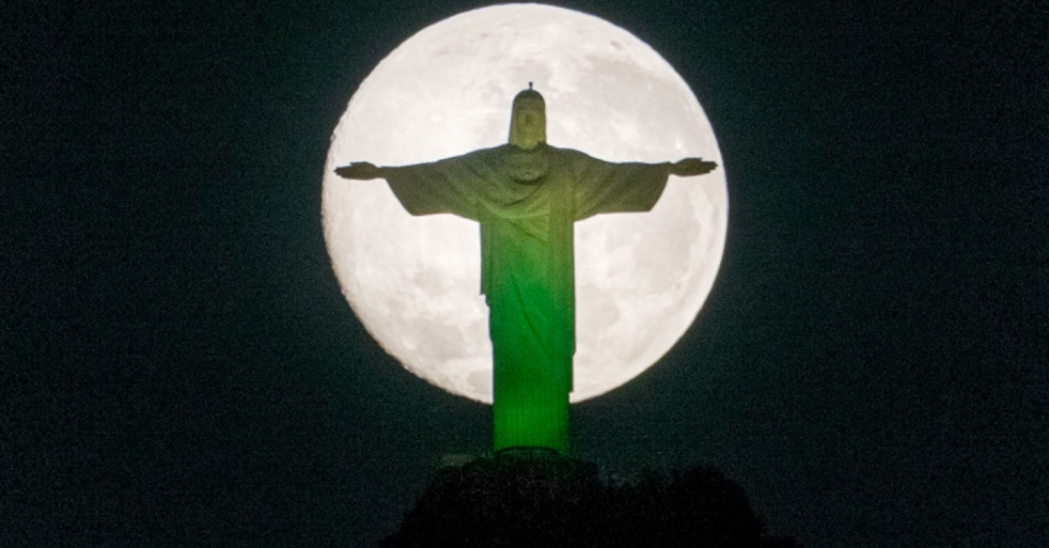 13;jul.2014 - A lua cheia surge atrás da estátua do Cristo Redentor, no Rio de Janeiro. O fenônemo da superlua ficou evidente na cidade até o início da manhã. A superlua ocorre quando a Lua se aproxima da órbita da Terra, fazendo com que ela pareça maior e mais brilhante do que o normal