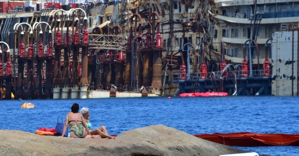 13.jul.2014 - Mulheres tomam banho de sol nas pedras em frente ao navio Costa Concordia, que naufragou há dois anos e meio em uma praia na ilha de Giglio, na Itália. Autoridades italianas aprovaram as operações para levantar e rebocar o navio a partir de sua base. O naufrágio do navio deixou 32 mortos
