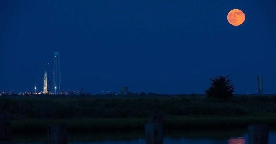 13.jul.2014 - Superlua pode ser observada à direita da Orbital Sciences Corporation, que lançou neste domingo (13) um foguete com suprimentos para a Estação Espacial Internaciona (ISS, sigla em inglês). A superlua ocorre quando a Lua se aproxima da órbita da Terra, fazendo com que ela pareça maior e mais brilhante do que o normal