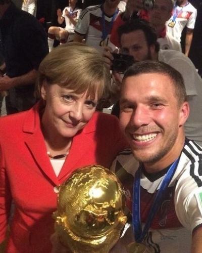 14.jul.2014 - A chanceler da Alemanha, Angela Merkel, faz selfie com o atacante reserva da seleção alemã Lukas Podolski. Ele foi um dos mais populares nas fotos da comemoração do tetra campeonato