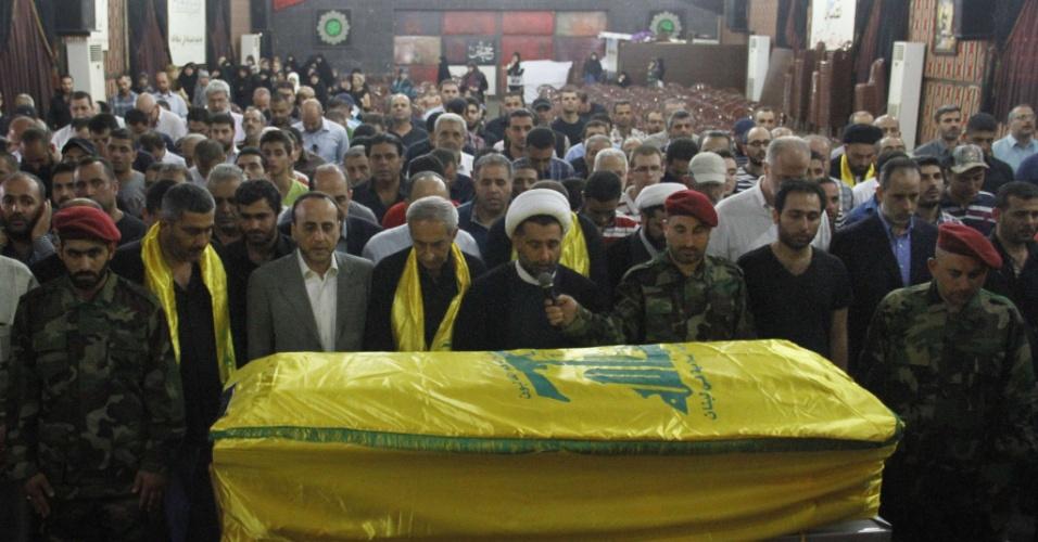 14.jul.2014 - Libaneses xiitas assistem ao funeral do combatente do Hezbollah Bilal Kesrwani no subúrbio de Beirute, nesta segunda-feira (14). Pelo menos 16 combatentes foram mortos em confrontos entre rebeldes sírios e o grupo militante xiita libanês Hezbollah na fronteira entre a Síria e o Líbano no fim de semana