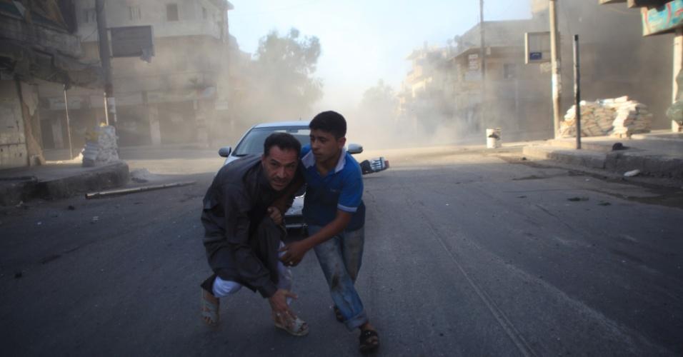 15.jul.2014 - Adolescente ajuda homem durante um ataque aéreo de forças leais ao governo no norte da cidade de Aleppo, na Síria, nesta terça-feira (15). Mais de 170 mil pessoas foram mortas em três anos de guerra civil, um terço delas civis, de acordo com o Observatório Sírio de Direitos Humanos