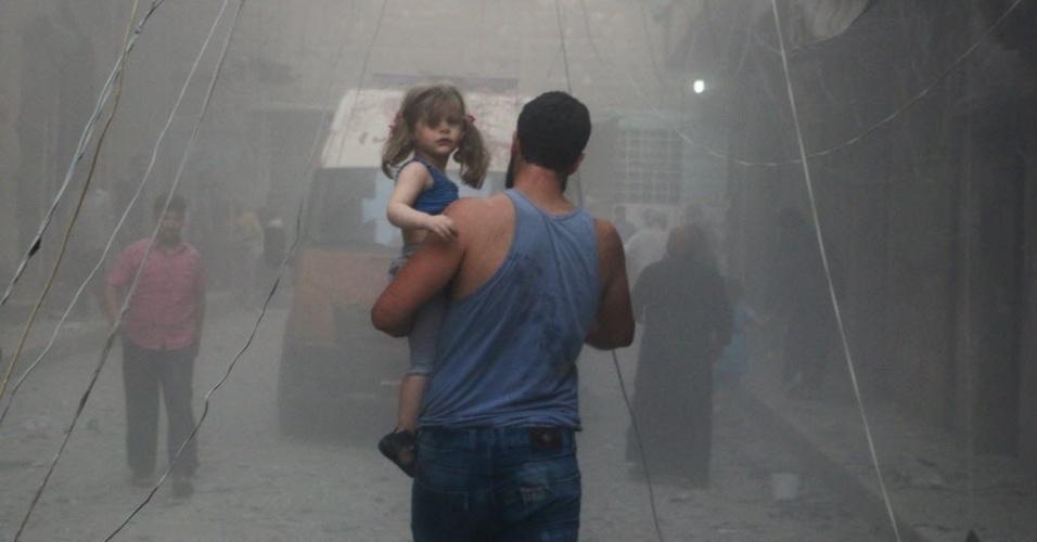 15.jul.2014 - Homem sírio carrega menina em uma rua coberta de poeira após um ataque aéreo das forças governamentais na cidade de Aleppo, nesta terça-feira (15). Mais de 170 mil pessoas foram mortas na guerra de três anos, um terço deles civis, de acordo com o Observatório Sírio para os Direitos Humanos
