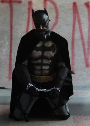 Manifestante vestido de Batman se acorrenta em frente a faixa durante protesto contra a prisão de ativistas envolvidos com manifestações na véspera da final da Copa do Mundo - Domingos Peixoto/Agência O Globo