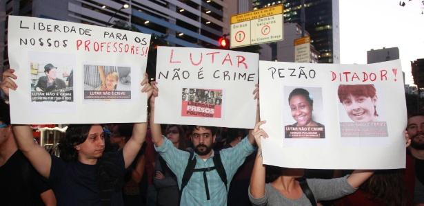 Manifestantes erguem cartazes durante protesto contra a prisão de ativistas envolvidos com manifestações na véspera da final da Copa do Mundo. O protesto acontece em frente ao TJ-RJ nesta terça-feira (15) - Domingos Peixoto/Agência O Globo