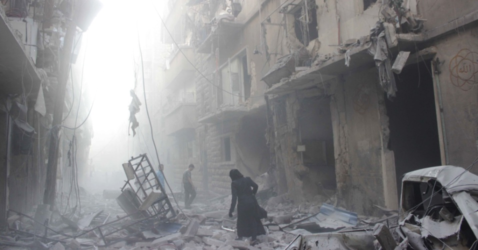 15.jul.2014 - Mulher síria caminha pelos escombros, após ataque aéreo liderado pelas forças do presidente Bashar al-Assad, nesta terça-feira (15), na cidade de Aleppo, no norte do país. Mais de 170 mil pessoas já morreram em três anos de guerra civil, uma terço delas civis, de acordo com o Observatório Sírio de Direitos Humanos