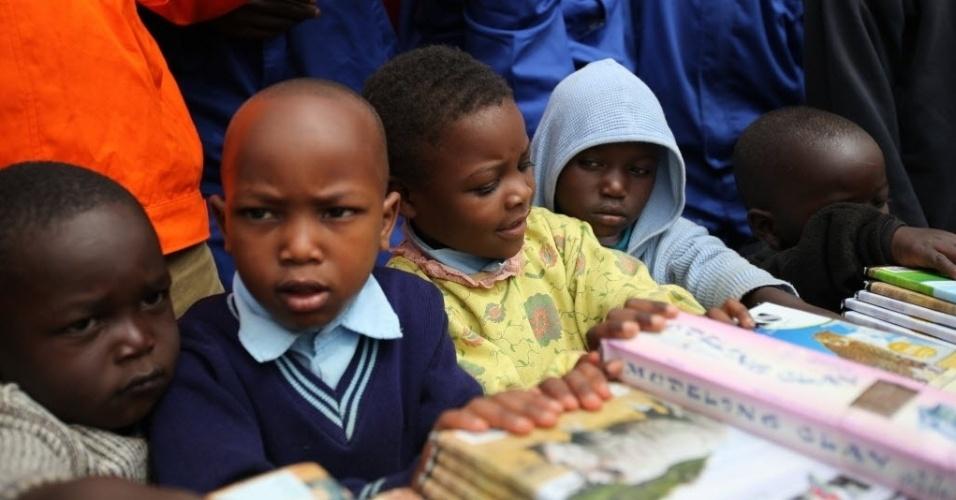 15.jul.2014 - Estudantes recebem doação de livros na favela Kibera, em Nairóbi, capital do Quênia. Além do material escolar, os alunos receberam alimentos. Kibera é considerada uma das maiores favelas do mundo