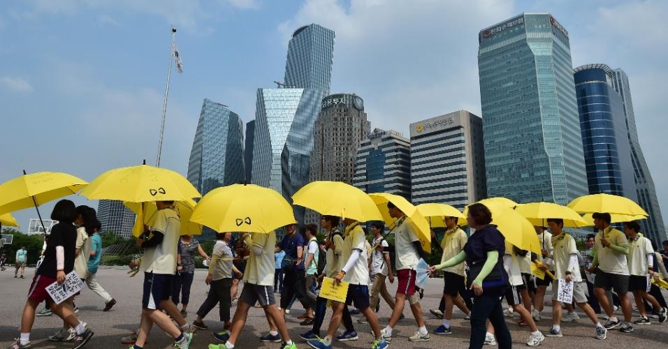 16.jul.2014 - Mais de 30 estudantes sobreviventes do naufrágio da balsa Seowl fazem uma passeata com guarda-chuvas amarelos perto do Parlamento, em Seul, na Coreia do Sul, para pedir um inquérito independente sobre a tragédia que deixou mais de 300 mortos