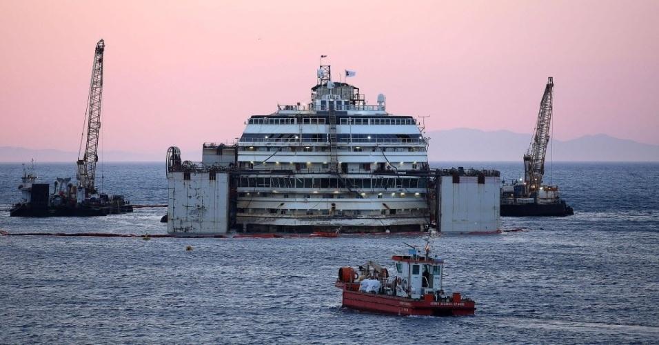 17.jul.2014 - Trabalhadores participam de operação para mover o cruzeiro Costa Concordia, nesta quinta-feira (17), no porto da Ilha Giglio, na Itália. O navio voltou a flutuar após uma operação com plataformas artificiais para apoiá-lo temporariamente. Com o auxílio de rebocadores, a embarcação poderá percorrer 370 quilômetros até Gênova