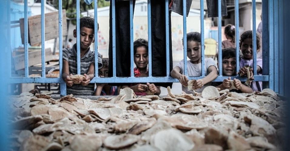 18.jul.2014 - Crianças recolhem alimentos em uma Agência das Nações Unidas para os refugiados da Palestina no Próximo Oriente, na cidade de Gaza, nesta sexta-feira (18). Cerca de 300 palestinos foram mortos e 2.100 feridos na atual escala ofensiva militar de Israel contra a faixa de Gaza