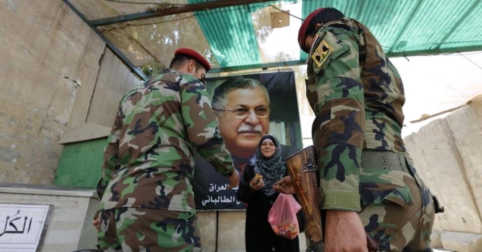 19.jul.2014 - Mulher iraquiana distribui doces para soldados em frente à sede da União Patriótica do Curdistão (PUK), em Bagdá. O presidente do Iraque, Jalal Talabani (no cartaz), é esperado após 18 meses de recuperação na Alemanha, depois de sofrer um acidente vascular cerebral
