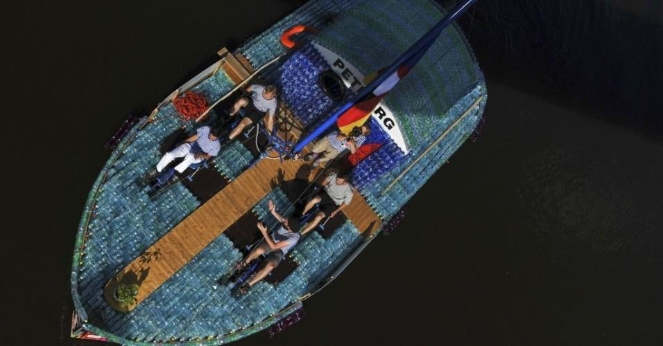 20.jul.2014 - Jovens pedalam barco feito de garrafas de plástico, no rio Elba, na República Tcheca. A foto foi tirada no dia 12 de julho e divulgada neste domingo (20). O barco de 10 metros de comprimento, construído por dois dos garotos da foto, tem 5.000 garrafas de plástico presas em uma base de madeira. Os homens pretendem pedalar de sua cidade natal Nymburk, na República Tcheca, descendo o rio Elba até Hamburgo, na Alemanha, para chamar a atenção para a crescente poluição de plásticos na Europa