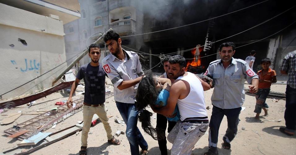 20.jul.2014 - Palestinos resgatam uma garota ferida durante os bombardeios israelenses à Rafah, no sul da faixa de Gaza. Pelo menos 40 palestinos morreram nos ataques deste domingo (20), elevando para cerca de 400 o número de mortos desde o reinício dos conflitos entre israelenses e palestinos. A grande maioria dos mortos é palestinos e composta por crianças e mulheres, segundo autoridades de Gaza