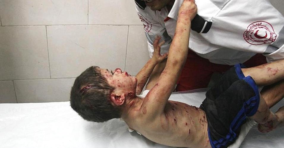 20.jul.2014 - Menino palestino se agarra ao paramédico no Hospital Shifa, na faixa de Gaza, após ser trazido com ferimentos causados por bombardeio das forças de Israel. Segundo um site de notícias palestino, o menino gritava perguntando: 'Onde está meu pai?'