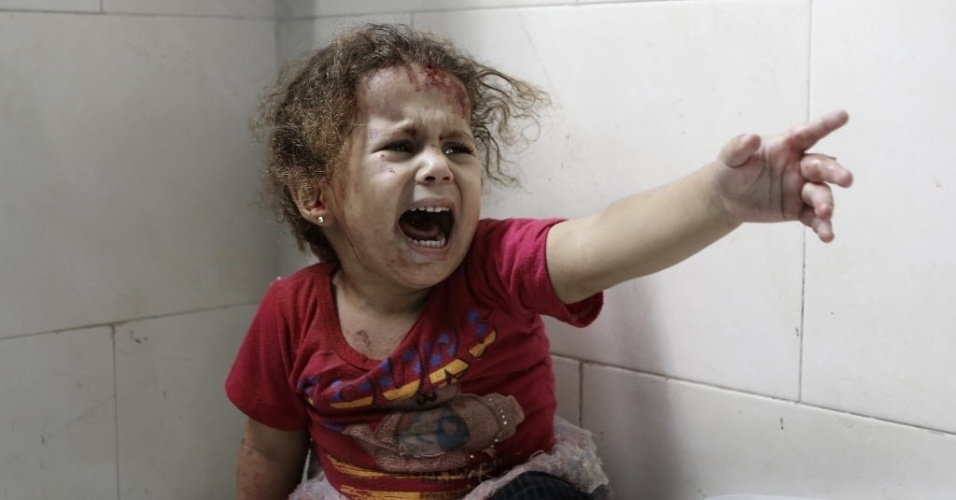 21.jul.2014 - Criança palestina grita na sala de emergência do hospital Shifa depois de tanques israelenses dispararem contra sua casa na faixa de Gaza. Cerca de 500 palestinos foram mortos, incluindo quase 100 crianças, em duas semanas de conflito