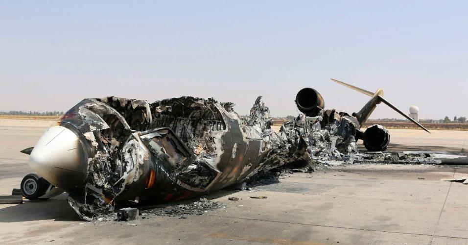 21.jul.2014 - Os destroços de uma aeronave queimada durante bombardeio permanecem no aeroporto internacional de Tripoli,na Líbia, nesta segunda-feira (21). Intensos combates eclodiram no domingo (20) no entorno do aeroporto, onde milícias rivais têm lutado pelo controle local, matando ao menos quatro pessoas e forçando milhares a deixarem suas casas