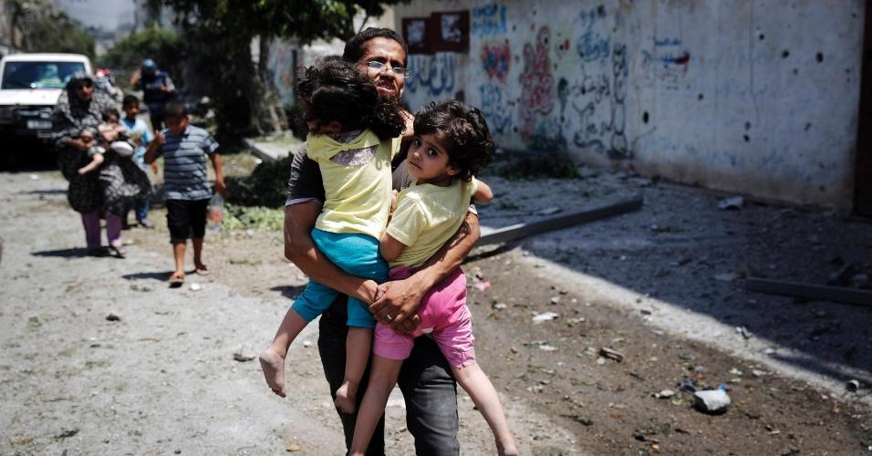 20.jul.2014 - Palestino carrega criança enquanto foge do bairro Shejaia, na faixa de Gaza, durante bombardeio israelense, neste domingo (20)
