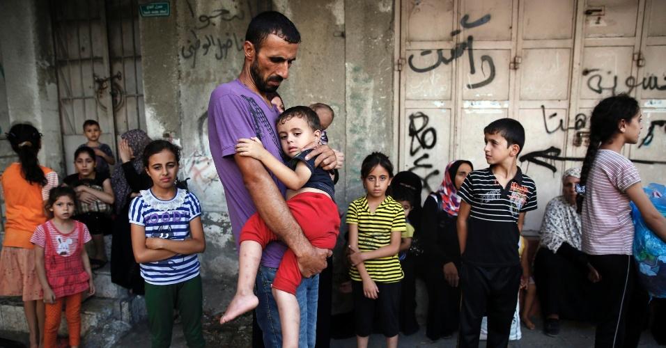 20.jul.2014 - Palestino carrega criança enquanto foge do bairro Shujayeh, na faixa de Gaza, durante bombardeio israelense, neste domingo (20)