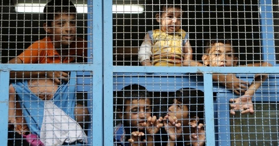 23.jul.2014 - Crianças palestinas de Beit Hanun, no norte da faixa de Gaza, observam por trás de janela de uma sala de aula em uma escola da ONU, no campo de refugiados de Jabalia, onde as famílias deslocadas se abrigaram depois de fugir de combates entre Hamas e Israel