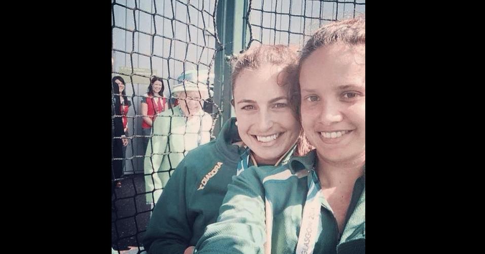 A usuária @_JaydeTaylor postou uma foto no Twitter em que a rainha Elizabeth, da Inglaterra, aparece na imagem ao fundo. As mulheres na imagem, Jayde Taylor (esq.) e Brooke Peris (dir.), são jogadores da seleção feminina de hóquei na grama da Austrália, que disputa os Jogos de Commonwealth no país