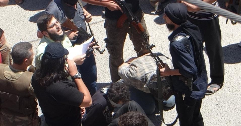 25.jul.2014 - Combatentes rebeldes se preparam para executar dois homens, supostamente condenados por um tribunal religioso liderado pela Frente Islâmica, pelos crimes de detonar vários carros-bomba na província de Idlib, na Síria