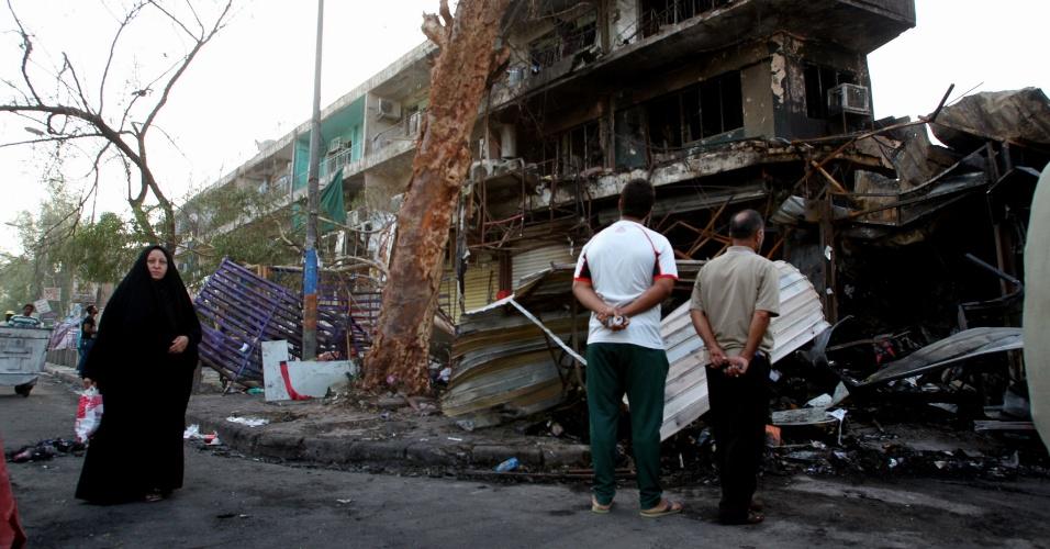 25.jul.2014 - Iraquianos observam, nesta sexta-feira (25), local de explosão ocorrida na noite anterior no distrito de Karrada, de maioria xiita, de Bagdá (Iraque). Explosões de dois carros-bomba causaram a morte de pelo menos 13 pessoas na capital iraquiana. As explosões se concentraram em Karrada, bairro repleto de lojas e restaurantes, logo após o momento em que as pessoas se reúnem para o desjejum do Ramadã - mês sagrado do islã em que muçulmanos fazem jejum entre o nascer e o por-do-sol