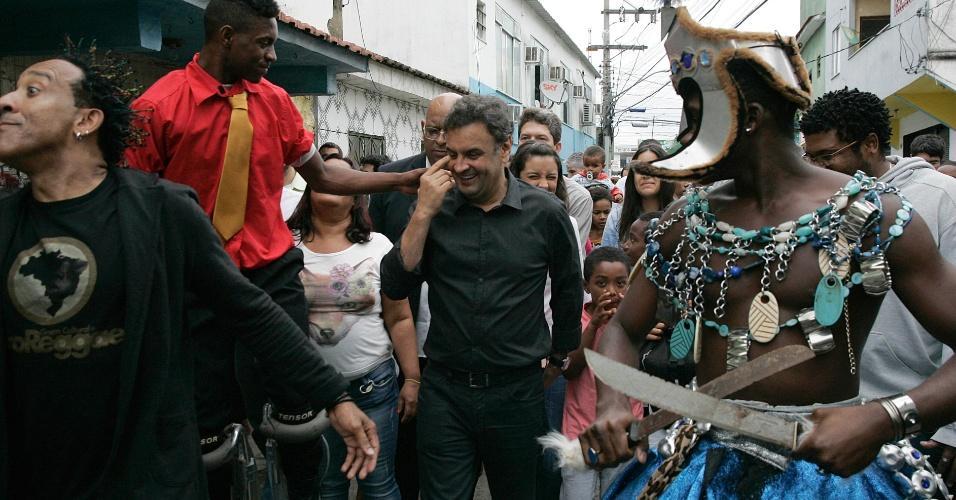 """25.jul.2014 - O candidato do PSDB à presidência da República, Aécio Neves, caminha em rua da favela Vigário Geral, na zona norte do Rio de Janeiro. Aécio assistiu à apresentação do grupo AfroReggae. Ele disse que a presidente Dilma Rousseff, candidata à reeleição pelo PT, tem tido """"dificuldade de se apresentar à população"""" neste início de campanha e que, por isso, tem privilegiado reuniões em locais fechados, cercada de aliados"""
