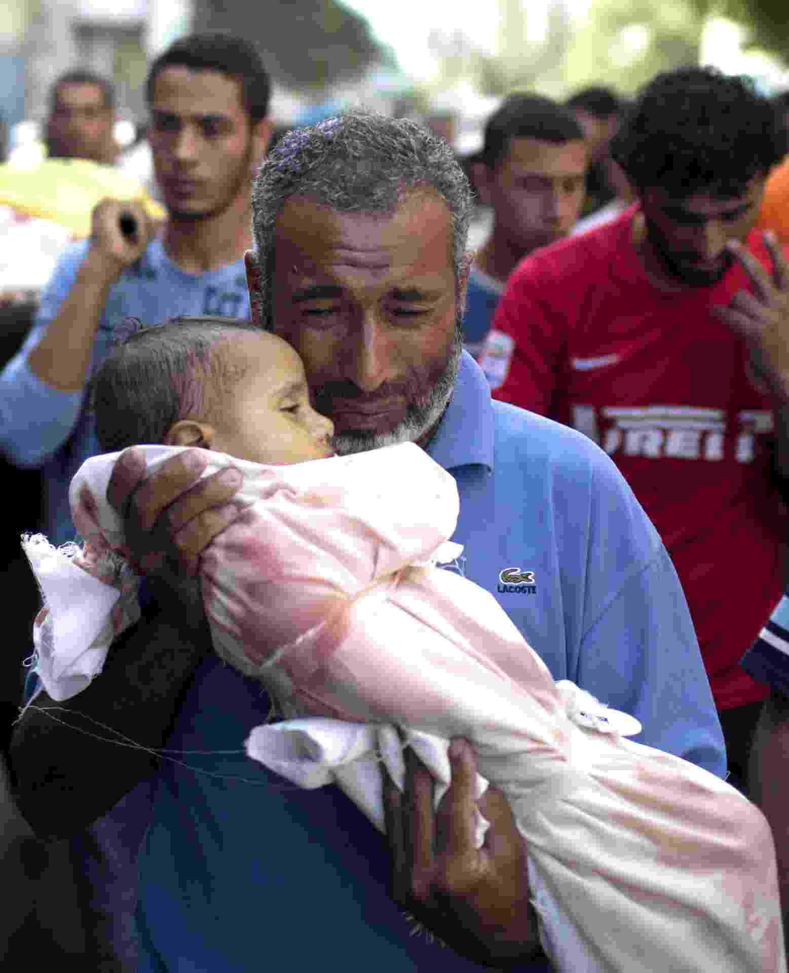 25.jul.2014 - Palestino carrega o corpo de bebê de um ano de idade, morto por causa dos ferimentos sofridos após o ataque de uma escola da ONU em Beit Hanun, norte da Faixa de Gaza, por um tanque israelense. Quinze pessoas morreram quando as forças de Israel atingiu a escola da ONU, usada como abrigo contra os ataques a Gaza, elevando o número de palestinos no 17 º dia de conflito a quase 800 pessoas - Mahmud Hams/AFP