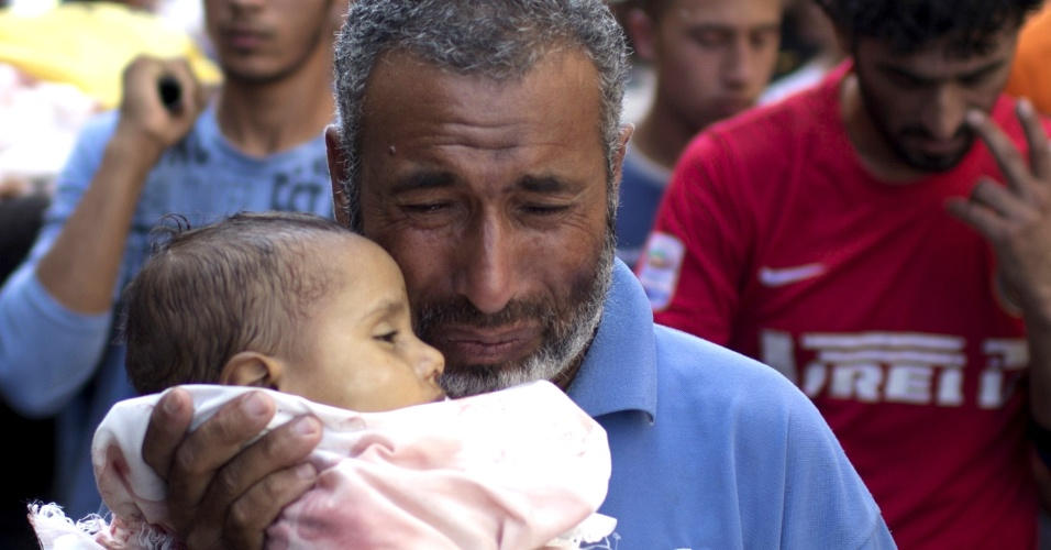 25.jul.2014 - Palestino carrega o corpo de bebê de um ano de idade, morto por causa dos ferimentos sofridos após o ataque de uma escola da ONU em Beit Hanun, norte da Faixa de Gaza, por um tanque israelense. Quinze pessoas morreram quando as forças de Israel atingiu a escola da ONU, usada como abrigo contra os ataques a Gaza, elevando o número de palestinos no 17 º dia de conflito a quase 800 pessoas