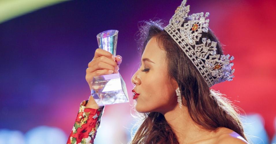 26.jul.2014 - A modelo Sharr Htut Eaindra (centro) beija troféu após ser eleita miss universo Mianmar 2014, durante desfile no Teatro Nacional da cidade de Rangum