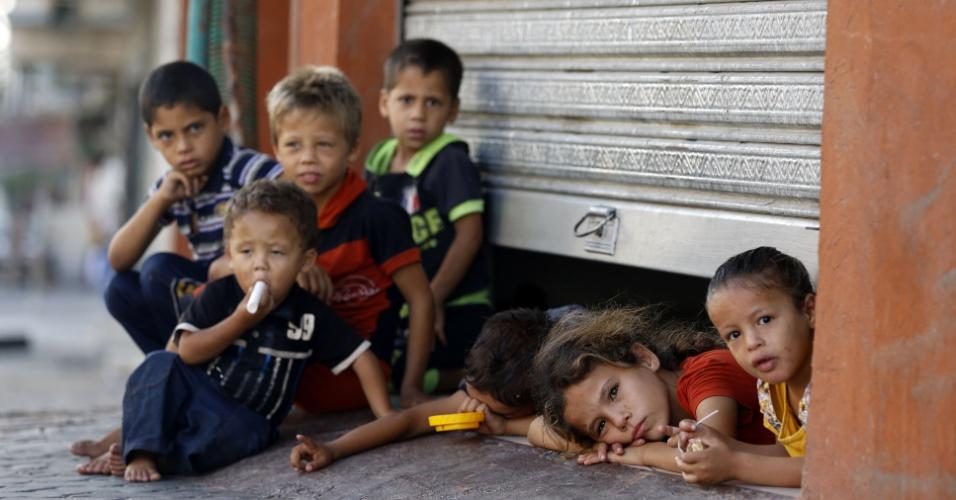 26.jul.2014 - Crianças palestinas sentam perto da porta entreaberta de uma loja que suas famílias fazem de abrigo em Gaza. O número de palestinos mortos na ofensiva israelense subiu na noite deste sábado (26) para 1.147, e o de feridos, a mais de 6.000. Mais de 800 das mortes, incluindo mais de 150 crianças, ocorreram durante a atual incursão terrestre, iniciada há nove dias