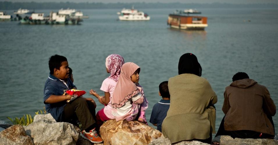 26.jul.2014 - Família indonésia espera por balsa para ir para casa por ocasião do festival Eid al-Fitr, em Port Klang, nos arredores de Kuala Lumpur. Um grande número de indonésios deixa a Malásia para celebrar o festival durante os últimos dias do mês de jejum do Ramadã, que acaba em 2014 acaba em 28 de julho