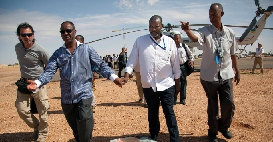 26.jul.2014 - Felix Ngoma (camisa azul listrada), funcionário da Organização Internacional para as Migrações (OIM) é recebido pelo vice-chefe da Unamid (missão de paz mista da ONU e União Africana), Abiodun Oluremi Bashua (segundo à esq.), no  aeroporto El Fasher, em Darfur do Norte, no Sudão. Ngoma foi libertado nesta sexta-feira (25) após 20 dias no cativeiro