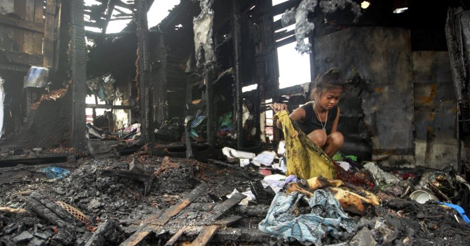 26.jul.2014 - Menina filipina busca por pertences após incêndio atingir durante a madrugada a favela Tondo, em Manila. De acordo com os bombeiros, o fogo deixou mais de 300 famílias desabrigadas e foi causado por uma lâmpada de querosene