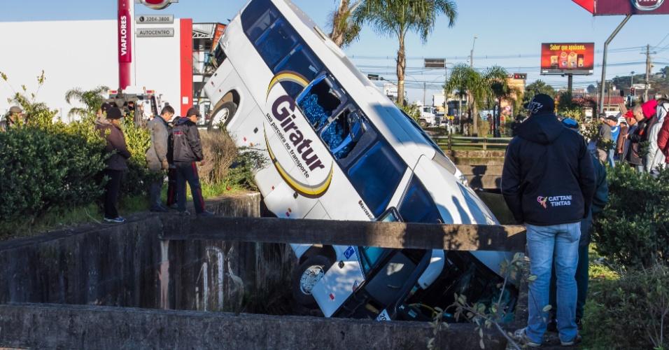 26.jul.2014 - Um ônibus caiu no vão do arroio Dal Bó, em Caxias do Sul (RS), após se envolver em acidente com um caminhão quando trafegava pela Perimetral Norte, na manhã deste sábado (26). Ao atingido pelo caminhão, o motorista perdeu o controle do veículo e bateu em um poste, até cair no espaço que fica no centro da avenida. O ônibus levava 10 funcionários de uma empresa. O motorista sofreu ferimentos leves