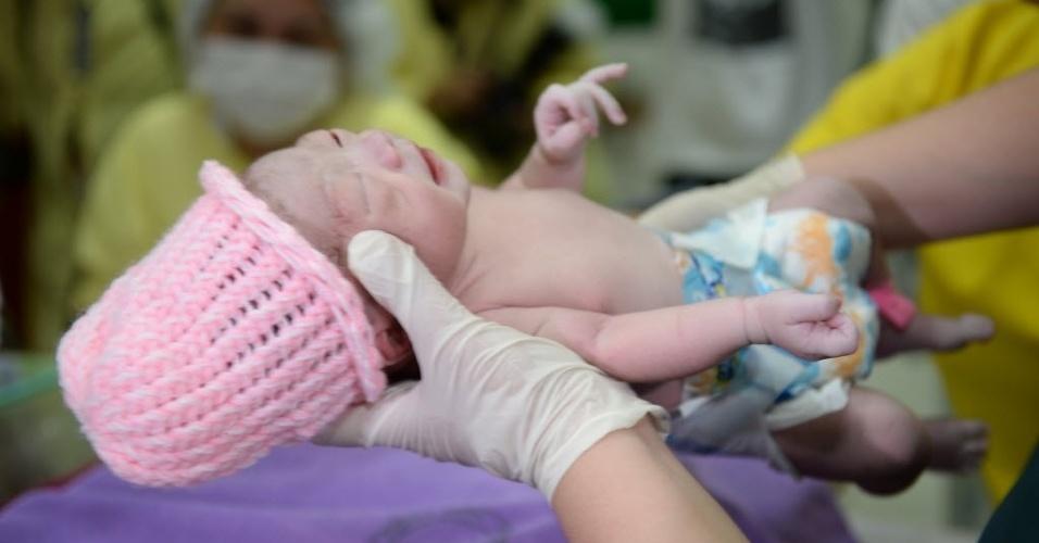 27.jul.2014 - Enfermeira segura o bebê de número 100 milhões nascido nas Filipinas