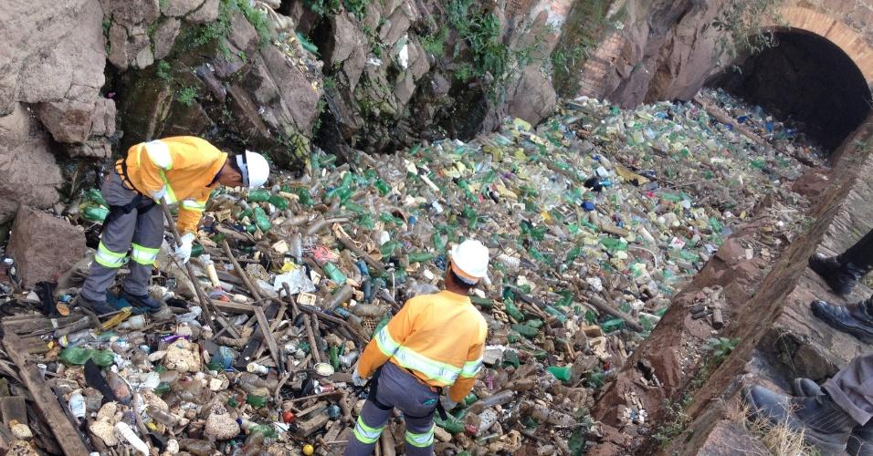 25.jul.2014 - Trabalhadores da Prefeitura Municipal de Salto retiram entulho do leito seco de um canal do rio Tietê