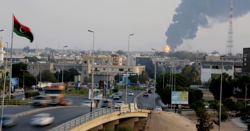 28.jul.2014 - Coluna de fumaça emana do local de ataque a um armazém de combustível em Trípoli, na Líbia, nesta segunda-feira (28). A violência entre milícias rivais se espalha Trípoli e Bengasi, umas das maiores cidades líbias, enquanto se multiplicam as chamadas de diferentes governos para que seus cidadãos abandonem o país