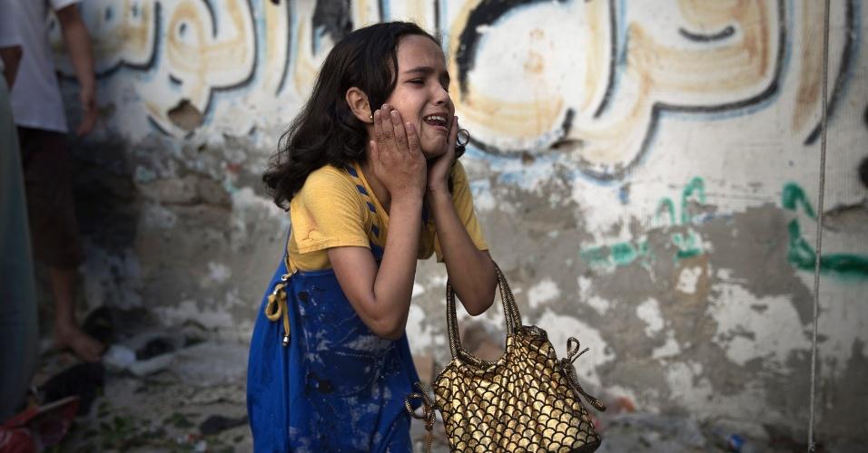 """28.jul.2014 - Garota palestina se assusta com explosão, nesta segunda-feira (28), em praça na faixa de Gaza. O premiê de Israel, Benjamin Netanyahu, disse em pronunciamento na TV que os israelenses devem """"se preparar para uma campanha prolongada"""" contra o Hamas na faixa de Gaza"""