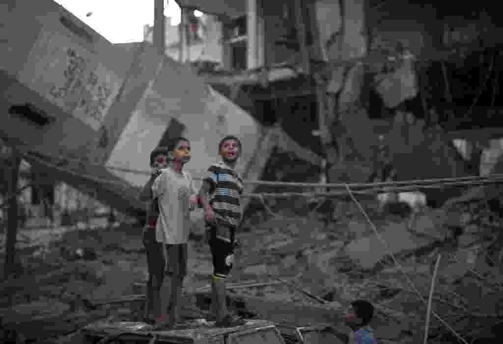 30.jul.2014 - Crianças palestinas caminham sob minarete de uma mesquita que desabou após ataques israelenses na faixa de Gaza, nesta quarta-feira (30). O templo foi um dos alvos do bombardeio da última noite. Nesta manhã, ao menos 20 palestinos foram mortos e 50 ficaram feridos em um novo ataque a uma escola da ONU que abrigava refugiados - Mahmud Hams/AFP