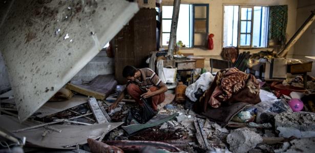 Observador palestino recolhe restos em sala de aula de escola da ONU bombardeada em Gaza. A instituição mantida pela UNRWA (Agência das Nações Unidas de Assistência aos Refugiados da Palestina funcionava como abrigo para refugiados