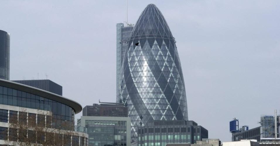 """30.jul.2014 - Um dos prédios mais famosos de Londres, o """"The Gherkin"""", foi colocado à venda por 650 milhões de libras esterlinas (cerca de R$ 2,4 bilhões), informou a agência imobiliária Savills, uma das responsáveis pela comercialização do local, na terça-feira (29). Conhecido por sua arquitetura que lembra uma bala de revólver, possui 40 andares, cerca de 47 mil metros quadrados e foi inaugurado em 2004"""