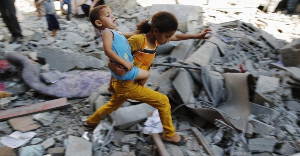 1º.ago.2014 - Garota palestina carrega o irmão pelos escombros de casas destruídas por mísseis israelenses no campo de refugiados de Burij, na faixa de Gaza, nesta sexta-feira (1º). O Exército de Israel e o grupo radical Hamas voltaram a trocar ataques, quebrando o cessar-fogo de 72 horas anunciado na quinta (31). Segundo os palestinos, após o cessar-fogo, pelo menos 27 foram mortos em um ataque israelense próximo a cidade de Rafah