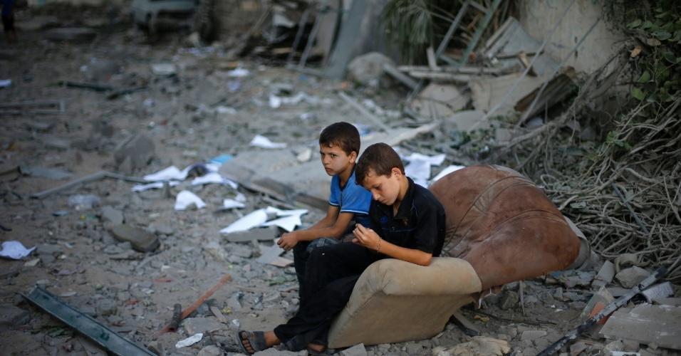 2.ago.2014 - Meninos palestinos se sentam em sofá do lado de fora de sua casa, que foi destruída em um ataque aéreo israelense, na Cidade de Gaza. A trégua de 72 horas entre Israel e o grupo Hamas na faixa de Gaza durou poucas horas e deixou mais de 100 palestinos mortos nesta sexta-feira (1º), após a suposta captura de um suboficial israelense em Rafah.