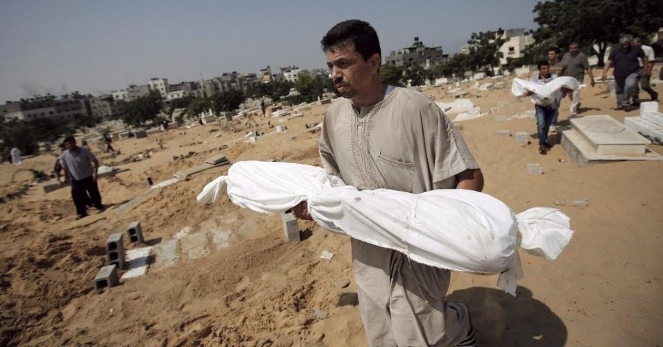2.ago.2014 - Palestino carrega o corpo de uma criança para enterrá-lo em um cemitério no norte da faixa de Gaza. Criança foi morta junta com dois irmãos e os pais em um ataque aéreo israelense