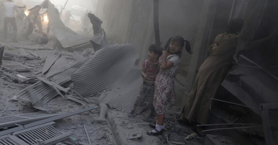 3.ago.2014 - Crianças se assustam perto de escombros após ataques aéreos por parte das forças leais ao ditador da Síria, Bashar al-Assad, neste domingo (3), perto de Damasco