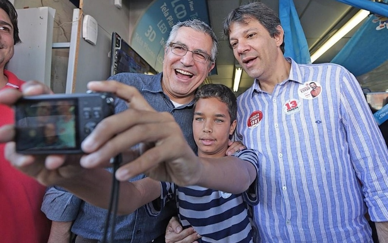 "3.ago.2014 - Durante uma caminhada pelas ruas do Grajaú, na zona sul de São Paulo, o candidato ao governo do Estado pelo PT, Alexandre Padilha (à esq.), tirou uma ""selfie"" com um menino do bairro na tarde deste domingo (3). O prefeito da capital paulista, Fernando Haddad, que participa da campanha de Padilha também entrou na foto"