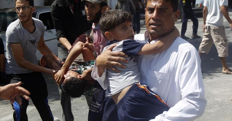 3.ago.2014 - Palestino carregam crianças feridas após ataque israelense em escola administrada pela ONU, na faixa de Gaza. Ao menos de pessoas morreram e 30 ficaram feridas
