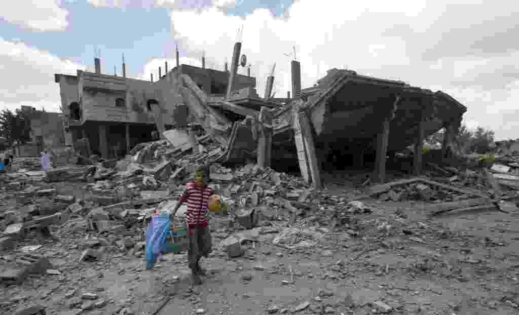 4.ago.2014 - Criança palestina carrega uma bola e uma gaiola de pássaros enquanto caminha sobre os escombros de um edifício, próximo ao campo de refugiados de Rafah, no sul da faixa de Gaza. Trabalhadores da Defesa Civil e médicos estão no bairro à procura de vítimas da ofensiva israelense - Mahmud Hams/AFP