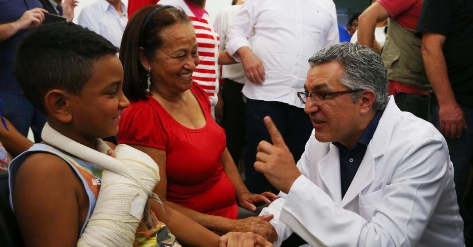 4.ago.2014 - O candidato do PT ao governo de São Paulo, Alexandre Padilha, veste jaleco durante visita a posto de saúde no Jardim Munhoz, em Osasco, na Grande São Paulo